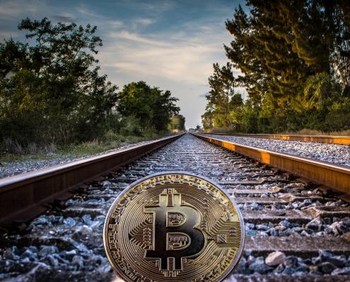 gold colored bitcoin on railroad